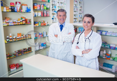 Smiling pharmacist and his trainee with arms crossed stock photo, Smiling pharmacist and his trainee with arms crossed in the pharmacy by Wavebreak Media