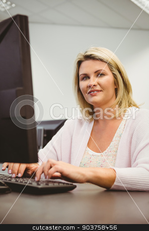 Mature student using laptop looking at camera stock photo, Mature student using laptop looking at camera in the office by Wavebreak Media