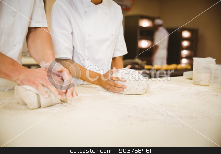 Team of bakers kneading dough stock photo, Team of bakers kneading dough in a commercial kitchen by Wavebreak Media