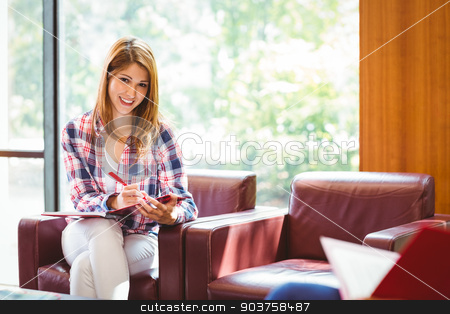 Happy student sitting on couch writing smiling at camera stock photo, Happy student sitting on couch writing smiling at camera at the university by Wavebreak Media