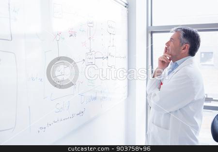 Focused scientist looking equation on whiteboard stock photo, Focused scientist looking equation on whiteboard in laboratory by Wavebreak Media