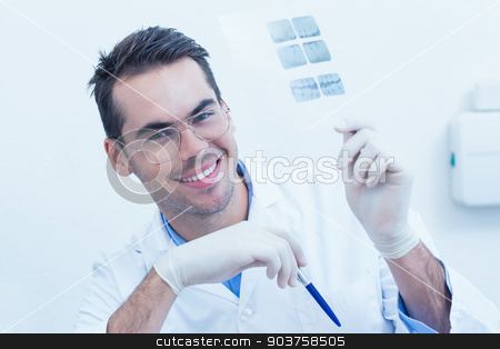 Smiling male dentist holding at x-ray stock photo, Portrait of smiling male dentist holding at x-ray by Wavebreak Media
