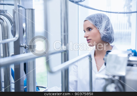 Portrait of a smiling scientist behind metal pipe stock photo, Portrait of a smiling scientist behind metal pipe in the factory by Wavebreak Media