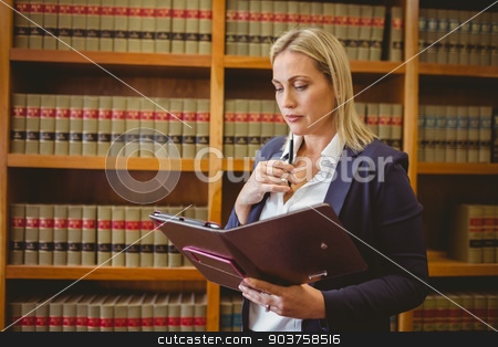 Thinking female librarian holding textbook stock photo, Thinking female librarian holding textbook in library by Wavebreak Media