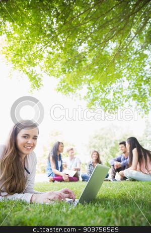 Happy student using her laptop outside stock photo, Happy student using her laptop outside at the university by Wavebreak Media