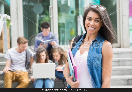 Pretty student smiling at camera outside stock photo, Pretty student smiling at camera outside at the university by Wavebreak Media