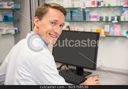 Happy pharmacist using the computer stock photo, Happy pharmacist using the computer at the hospital pharmacy by Wavebreak Media