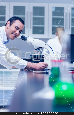 Science student working with microscope in the lab stock photo, Science student working with microscope in the lab at the university by Wavebreak Media