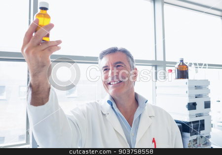 Smiling scientist in lab coat holding a chemical bottle stock photo, Smiling scientist in lab coat holding a chemical bottle in laboratory by Wavebreak Media
