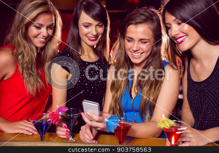 Pretty friends looking at smartphone together stock photo, Pretty friends looking at smartphone together at the nightclub  by Wavebreak Media
