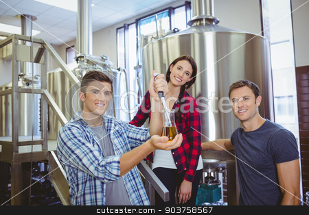 Man pouring beer into the beaker with a pipette stock photo, Man pouring beer into the beaker with a pipette in the factory by Wavebreak Media