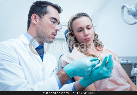 Male dentist teaching woman how to brush teeth stock photo, Male dentist teaching woman how to brush teeth in the dentists chair by Wavebreak Media