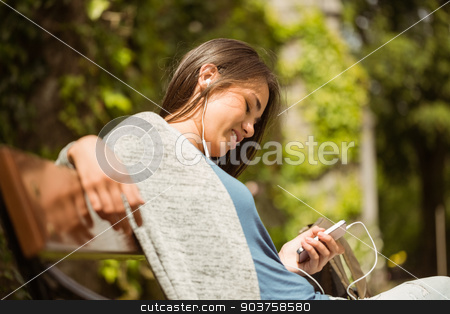 Smiling student sitting on bench text message on her mobile phon stock photo, Smiling student sitting on bench text message on her mobile phone in park at school by Wavebreak Media