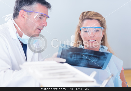 Dentist showing x-ray to his patient stock photo, Dentist showing x-ray to his patient at the dental clinic by Wavebreak Media