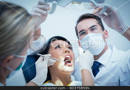 Dentist with assistant examining womans teeth stock photo, Male dentist with assistant examining womans teeth in the dentists chair by Wavebreak Media