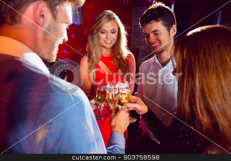 Happy friends toasting with champagne stock photo, Happy friends toasting with champagne at the nightclub  by Wavebreak Media