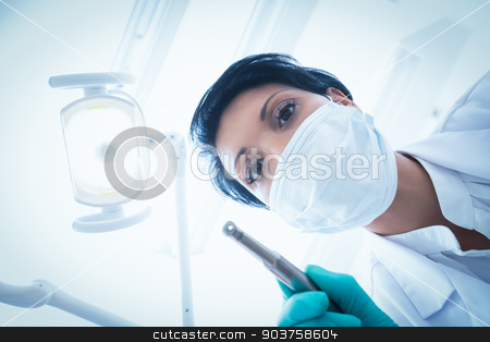 Female dentist in surgical mask holding dental drill stock photo, Portrait of female dentist in surgical mask holding dental drill by Wavebreak Media
