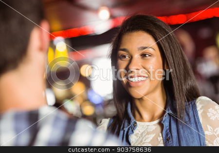 Happy friends standing chatting together stock photo, Happy friends standing chatting together in a bar by Wavebreak Media