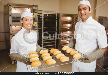 Team of bakers holding rack of rolls stock photo, Team of bakers holding rack of rolls in a commercial kitchen by Wavebreak Media
