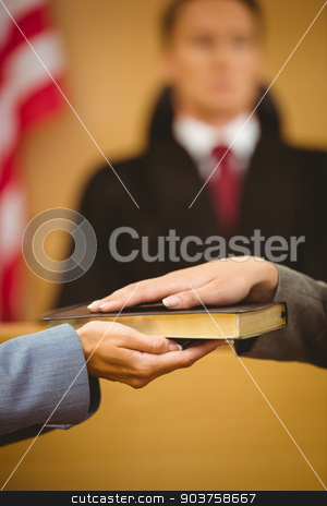 Witness swearing on the bible telling the truth stock photo, Witness swearing on the bible telling the truth in the court room by Wavebreak Media