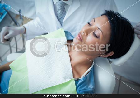 Close up of woman having her teeth examined stock photo, Close up of woman having her teeth examined by dentist by Wavebreak Media