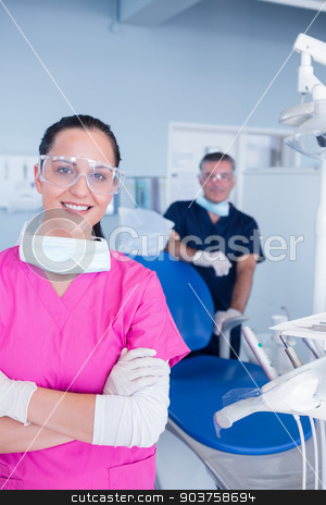 Smiling assistant and dentist behind her with protective glasses stock photo, Smiling assistant and dentist behind her with protective glasses at the dental clinic by Wavebreak Media