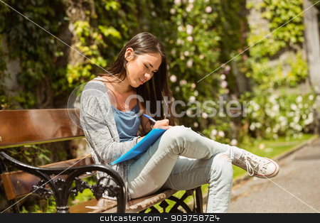 Smiling student sitting on bench and writing on notepad stock photo, Smiling student sitting on bench and writing on notepad in park at school by Wavebreak Media
