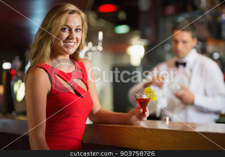 Pretty blonde smiling at camera with cocktail stock photo, Pretty blonde smiling at camera with cocktail in a bar by Wavebreak Media
