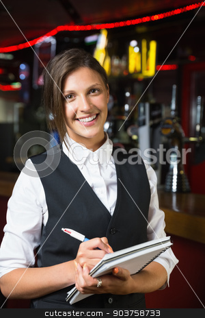 Happy barmaid smiling at camera taking notes stock photo, Happy barmaid smiling at camera taking notes in a bar by Wavebreak Media