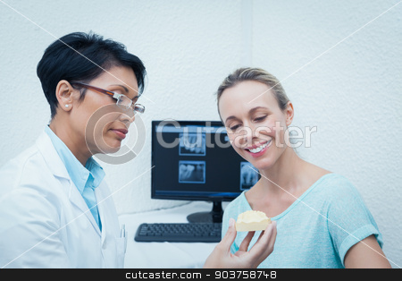 Dentist showing woman prosthesis teeth stock photo, Female dentist showing happy woman prosthesis teeth by Wavebreak Media