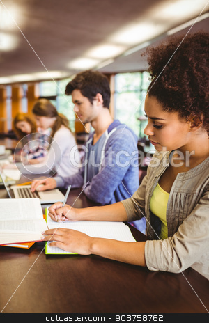 Focused students sitting in a line writing  stock photo, Focused students sitting in a line writing in library by Wavebreak Media