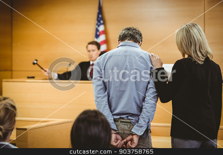 Judge about to bang gavel on sounding block stock photo, Judge about to bang gavel on sounding block in the court room by Wavebreak Media