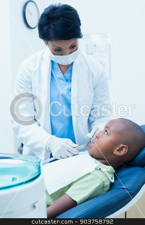 Female dentist examining boys teeth stock photo, Female dentist examining boys teeth in the dentists chair by Wavebreak Media