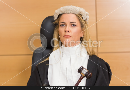Stern judge sitting and listening stock photo, Stern judge sitting and listening in the court room by Wavebreak Media