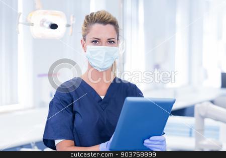Dentist in mask using her tablet and looking at camera stock photo, Dentist in mask using her tablet and looking at camera at the dental clinic by Wavebreak Media