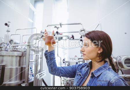 Stylish brunette in denim jacket looking at beaker of beer stock photo, Stylish brunette in denim jacket looking at beaker of beer in the factory by Wavebreak Media