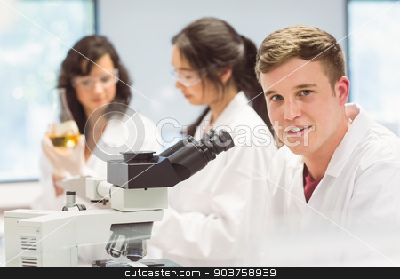 Science student looking through microscope in the lab stock photo, Science student looking through microscope in the lab at the university by Wavebreak Media