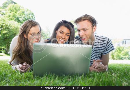 Happy students using laptop outside stock photo, Happy students using laptop outside at the university by Wavebreak Media