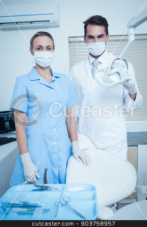 Portrait of dentists wearing surgical masks stock photo, Portrait of male and female dentists wearing surgical masks by Wavebreak Media