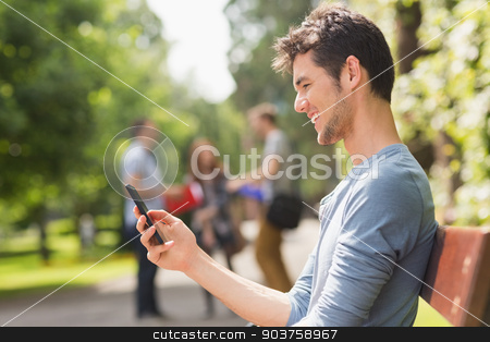 Handsome student sending a text outside stock photo, Handsome student sending a text outside at the university by Wavebreak Media