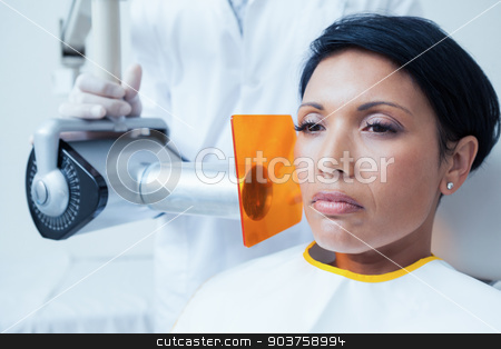 Serious young woman undergoing dental checkup stock photo, Serious young woman undergoing dental checkup in the dentists chair by Wavebreak Media
