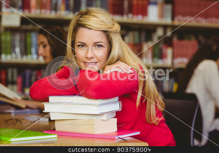 Smiling mature student leaning on a stack of books stock photo, Smiling mature student leaning on a stack of books in library by Wavebreak Media
