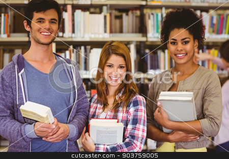 Students standing and smiling at camera holding books stock photo, Students standing and smiling at camera holding books in library by Wavebreak Media