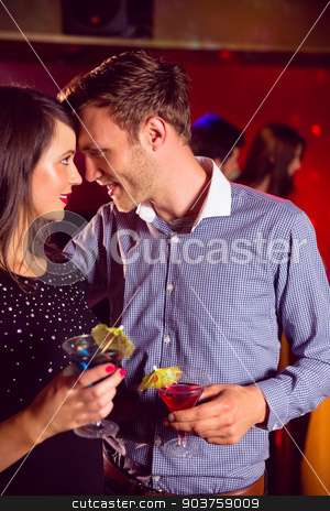 Cute couple drinking cocktails together stock photo, Cute couple drinking cocktails together at the nightclub  by Wavebreak Media