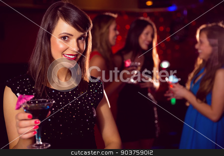 Pretty brunette drinking a cocktail stock photo, Pretty brunette drinking a cocktail at the nightclub  by Wavebreak Media