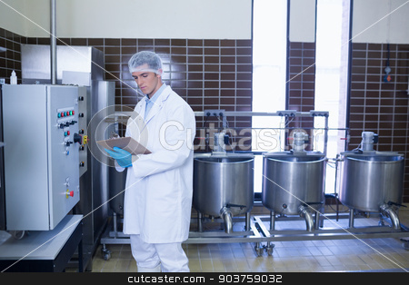 Focused biologist with safety gloves holding clipboard stock photo, Focused biologist with safety gloves holding clipboard in the factory by Wavebreak Media
