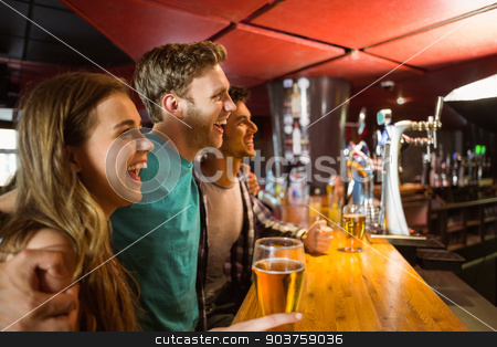 Smiling brown hair standing with arm around his friends stock photo, Smiling brown hair standing with arm around his friends by Wavebreak Media