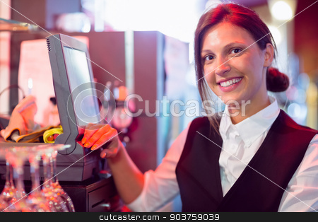 Happy barmaid using touchscreen till stock photo, Happy barmaid using touchscreen till in a bar by Wavebreak Media