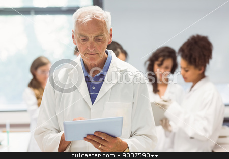 Science lecturer holding tablet pc in lab  stock photo, Science lecturer holding tablet pc in lab at the university by Wavebreak Media