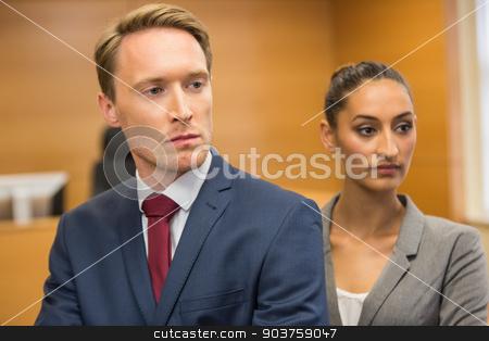 Stern lawyers looking ahead stock photo, Stern lawyers looking ahead in the court room by Wavebreak Media